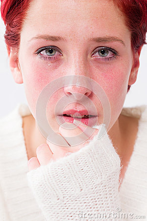 Depressed crying young redhead woman