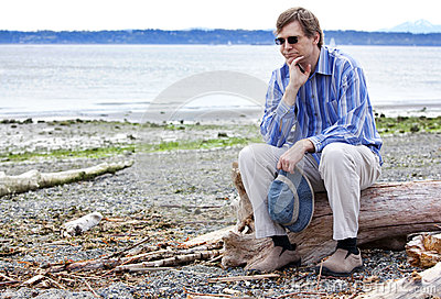Depressed man sitting on driftwood on beach