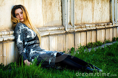 Depressed sad woman near grungy wall