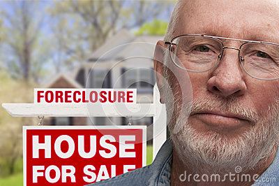 Depressed Senior Man in Front of Foreclosure Sign and House