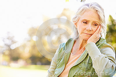 Depressed Senior Woman Sitting Outside Stock Photo