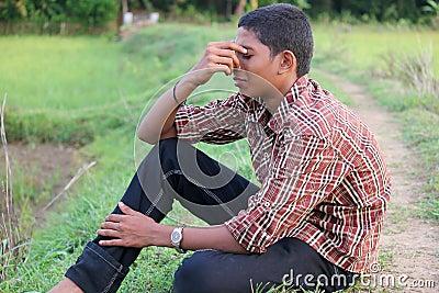 Teenaged boy sits looking depressed his head is resting on his hand