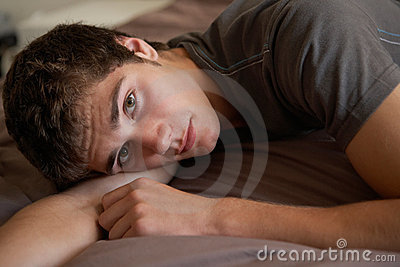 Depressed Teenage Boy Lying In Bedroom