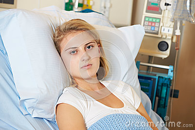 Depressed Teenage Female Patient Lying In Hospital Bed