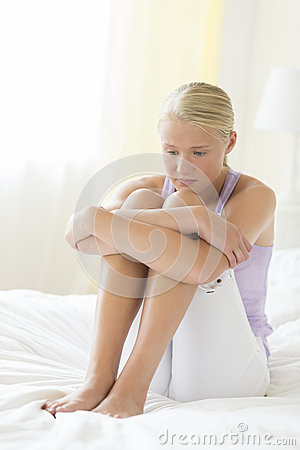 Depressed Teenage Girl Hugging Knees On Bed