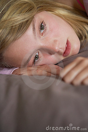 Depressed Teenage Girl Lying In Bedroom