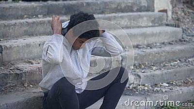 Depressieve jonge zwarte man die buiten zit, emotioneel misbruik, gezinsprobleem stock video