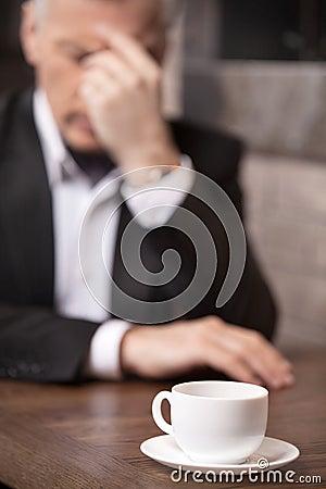 Deprimierter Geschäftsmann. Deprimierter reifer Geschäftsmann, der an t sitzt