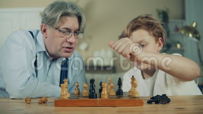 Der alte Mann und sein Enkel schauen sich Schachfiguren genau an stock video