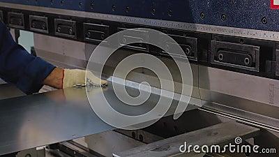 Der Betreiber f?gt ein Blatt des Metalls in die verbiegende Maschine ein und verbiegt es Der Prozess der Metallbehandlung Abschlu stock footage