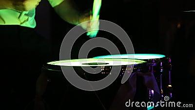 Der Drummer spielt mit Stöcken ein durchschnittliches Tempo auf leichten Trommeln Es ist dunkel herum stock video footage