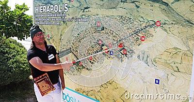 Der Führer auf der Karte zeigt und erzählt die Geschichte der Entstehung der Stadt Hierapolis stock footage