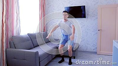 Der Funny Nerd Mann macht sich zu Hause im Wohnzimmer amüsieren Funny zieht kurze Hosen vor der Übung auf stock video
