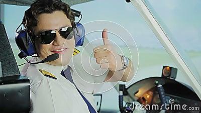 Der glückliche männliche Pilot in der Sonnenbrille lächelnd an der Kamera, machend greift herauf Handzeichen ab stock footage