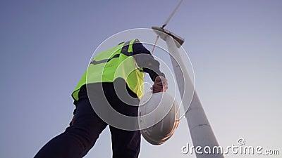 Der Ingenieur Hold in seinen Händen ein weißer Sturzhelm und Schritte nach vorn zur Windmühle vor ihm stock video