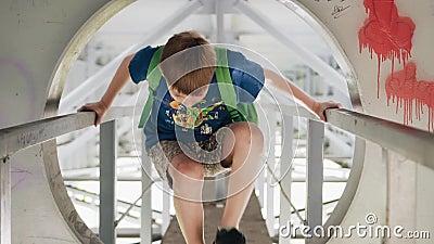 Der Junge geht entlang den Metallkorridor unter die Brücke Er klettert durch die Luke Kühle Gesamtlänge in der Bewegung stock video