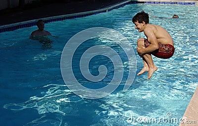Der Junge springend in das Pool