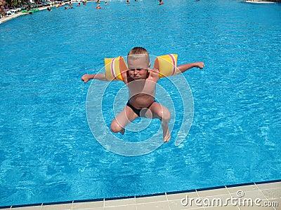 Der Junge springend in Swimmingpool