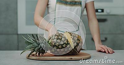 In der Küche schnitt eine Frau eine große Ananas mit einer großen Messernahaufnahme, Zeitlupe stock video