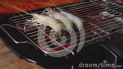 Der Küchenchef grillt die Garnelen auf dem Elektroherd stock footage