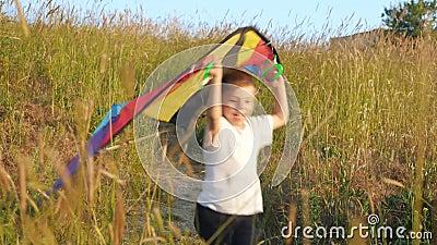 Der kleine Kinderjunge, der entlang Weg den im Freienlaufen und die Griffe spielen Drachen über seinem Kopf gewinnende Konzepte stock video