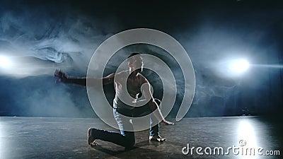 Der männliche Tänzer spielt einen Stunt-Jump mit einem Rotation-Rücken und einer Revolution in der Szene im Rauch im Scheinwerfer stock video footage
