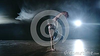 Der männliche Tänzer spielt einen Stunt-Jump mit einem Rotation-Rücken und einer Revolution in der Szene im Rauch im Scheinwerfer stock footage