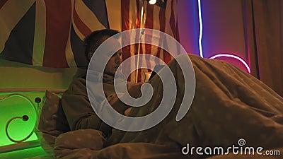 Der müde Mann liegt im Bett in einem Hoodie mit einem Handy in den Händen, das die sozialen Medien kontrolliert Ein 40-jähriger M stock video footage