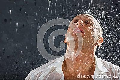 Der Mann, der nasses Hemd trägt, steht im Regen