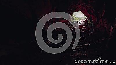 Der Mann, der in die Höhle hinunter geht und den Eingang hinter sich lässt, Extrem- und Sportkonzept Bestandsaufnahmen Tourist stock footage