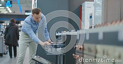 Der Mann im Hemd, zum der Tür der Spülmaschinengeräte im Speicher zu öffnen und mit anderen Modellen zu vergleichen, um das neue  stock video