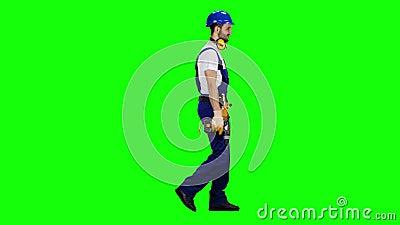 Der Mann, der von einer Baustelle arbeitet, kommt mit einem Bohrgerät in seinen Händen Grüner Bildschirm Weicher Fokus stock video