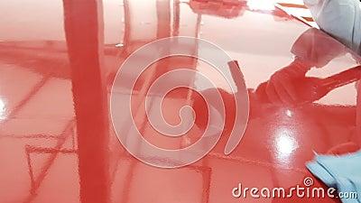 Der Prozess des Polierens des roten Teils Mechanik mit einem Rotationspolier auf einem roten Putz-Gemälde in einer Karosserie stock footage