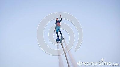Der selbstbewusste Flyboarder fliegt über Wasser gegen Himmel, streckt sich die Hand hoch, extreme sportliche Aktivität stock video