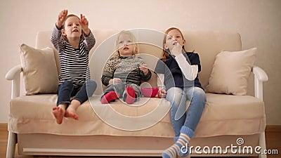 Der sonnige kleine Junge 3 Jahre alt sieht Karikaturen mit älteren Schwestern im Alter von 8 und 9 Jahren an Bruder und Schwester stock video