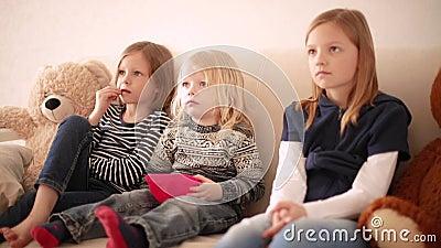 Der sonnige kleine Junge 3 Jahre alt sieht Karikaturen mit älteren Schwestern im Alter von 8 und 9 Jahren an Bruder und Schwester stock video footage