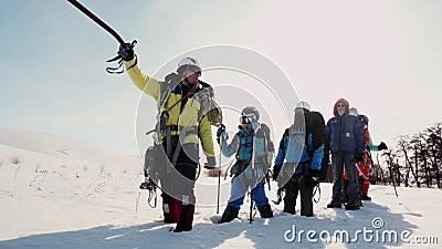 Der Spediteur zeigt die Eisaxt in Richtung ihrer Weise das Team steht im Schnee und war müde stock footage