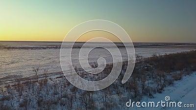 Der Zug fährt bei Sonnenuntergang durch schneebedeckte Felder stock video footage