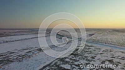 Der Zug fährt bei Sonnenuntergang durch schneebedeckte Felder stock footage