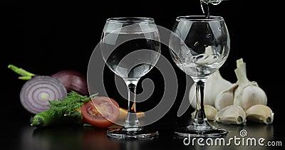 Derrame a vodca do ?lcool de uma garrafa em dois vidros disparados Fundo com vegetais vídeos de arquivo