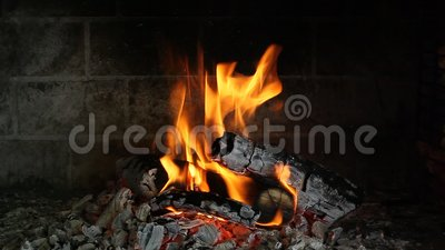 Des billes de bois brûlent dans une cheminée en brique dans l'obscurité clips vidéos