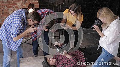 Des caméramans avec du matériel professionnel sur fond de canapés et de murs en briques prennent des photos de fillette en ce qui clips vidéos