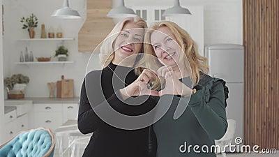 Des femmes caucasiennes mûres souriantes, debout dans une cuisine luxueuse, et des doigts fauchés en forme de coeur Femme âgée ri clips vidéos
