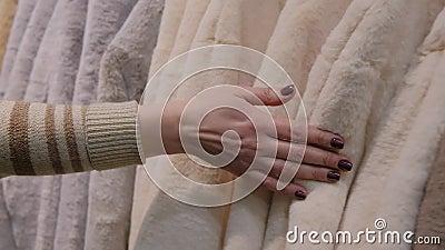 Des femmes se touchent à la main des vestes d'hiver en faux fourrure de luxe pour la vente d'hiver sur un étendoir dans un magasi banque de vidéos