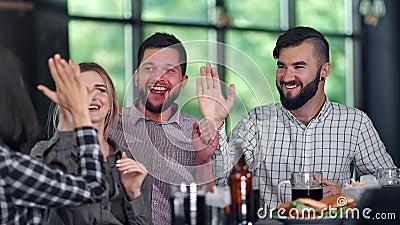 Des gens de groupe stupéfaits regardant le championnat de football au bar sportif avec de la bière fast food banque de vidéos
