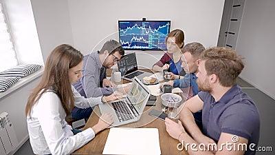 Des groupes de spécialistes travaillent dans une salle de bureau, s'assoient à une grande table, font une pause café clips vidéos