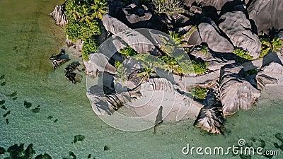 Des images volantes de la célèbre plage tropicale de l'Anse Source d'Argent à la lumière du jour ensoleillée Lagon peu profond à  banque de vidéos
