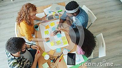 Des jeunes créatifs qui travaillent dans un projet réalisant un collage au bureau parlant banque de vidéos