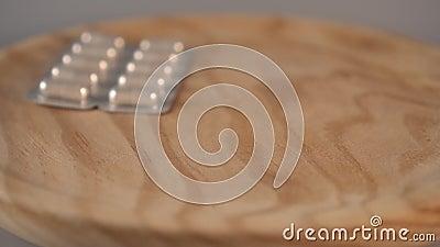 Des paquets de capsules médicales tombent d'en haut sur une surface en bois banque de vidéos