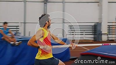 Des voûtes en pôle à l'intérieur - un homme en chemise jaune qui courait et saute au-dessus du bar banque de vidéos